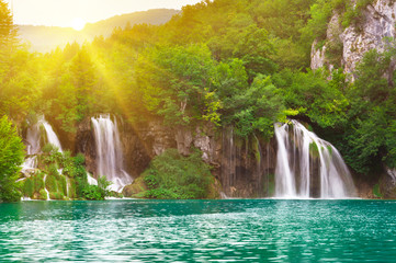 Waterfalls in national park in sun rays. Plitvice, Croatia