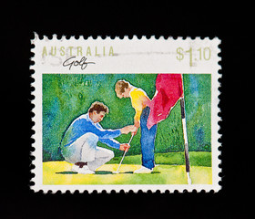 old stamp of boy being taught to play golf with clipping path