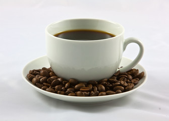 coffee cup on a suacer of beans