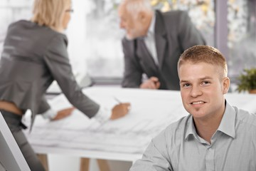 Young office worker with colleagues in background