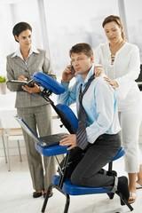 Occupied businessman getting massage