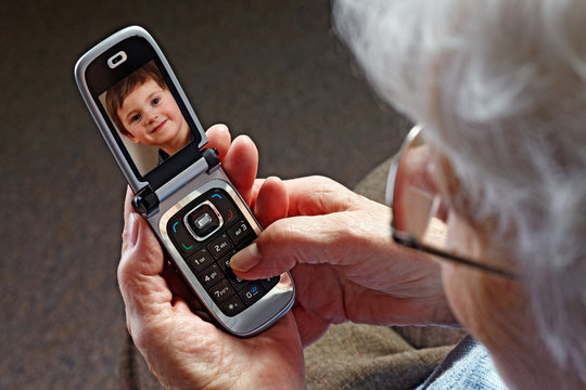 aged woman and grandson at the screen of a cell phone