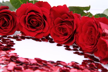 Red roses and heart shaped confetti on white background