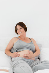 Pregnant woman cuddling her belly