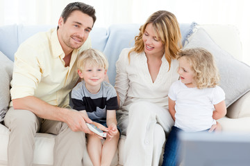 Adorable family watching tv