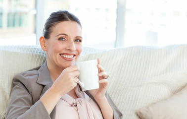 Happy businesswoman drinking a cup of coffee