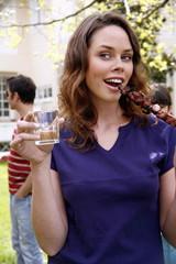 Woman eating souvlaki and drinking wine at a barbecue