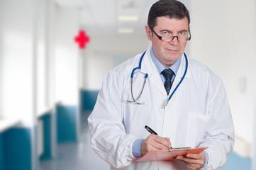 mature doctor writing at hospital