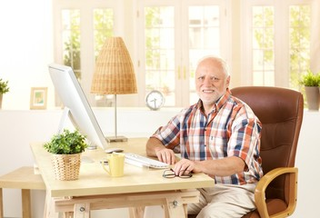 Senior man sitting at desk at home