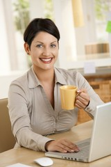 Young woman drinking tea at desk