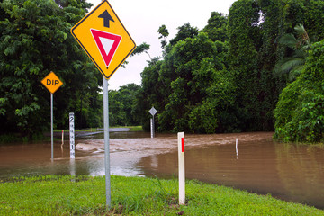 Flooded road with depth indicators and give way sign in Queensla