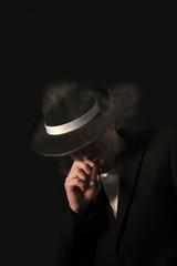 elegant gangster dressed in a black suit with cigar