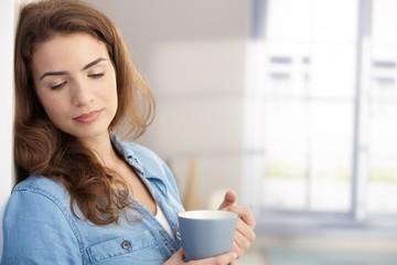Pretty female daydreaming drinking tea