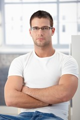 Sporty man wearing glasses sitting arms crossed