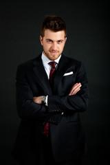 Confident businessman portrait on dark background