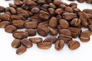 brown coffee beans scattered on a white background
