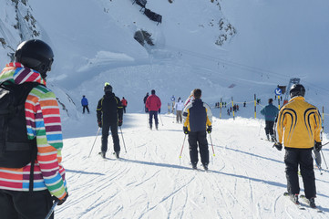 People skiing in european alps. Diverse clothing styles.