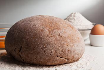 Homemade dough on a table with flour and egg