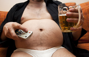 Overweight man sitting on the couch with a beer glass