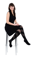 Girl in black dress sitting on a high chair, isolated