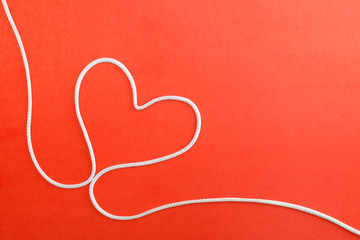 Heart made from rope on red paper background