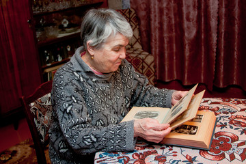 an elderly grey woman  looks over old photos