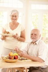 Portrait of happy senior couple at breakfast