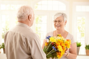 Smiling senior woman receiving bouquet