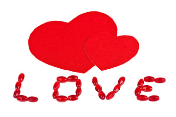 """The inscription """"Love"""" and two red textile hearts"""