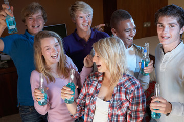 Group Of Teenage Friends Dancing And Drinking Alcohol