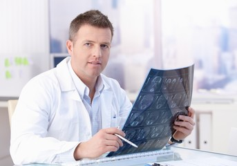 Middle-aged doctor studying x-ray image