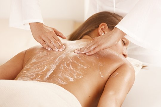 Masseur applying massage cream