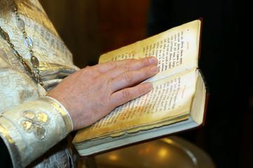 Bible in priest's hands