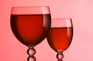 Wine glasses with wine on a pink background