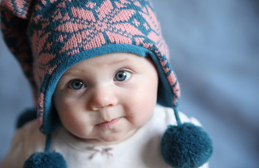 Baby with blue eyes in a winter cap