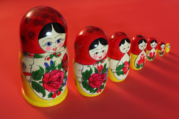 A set of Russian dolls on the red background.
