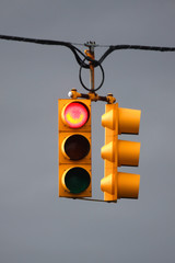 Red traffic light with overcast sky background
