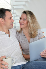 Couple at home using electronic tablet