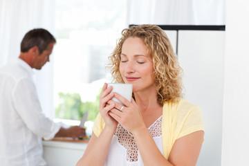 Pretty woman drinking tea in her kitchen