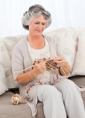 Senior woman knitting on her sofa