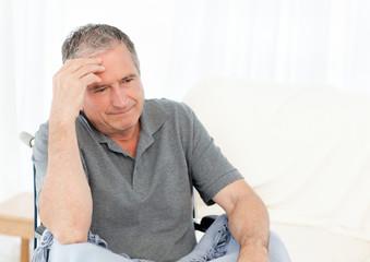 Senior in his wheelchair having a headache