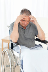 Senior in his wheelchair having a headache