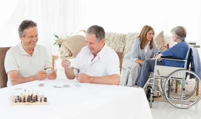 Men playing cards while their wifes are talking