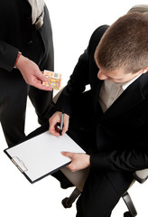 closeup of a businessman signing a contract beeing bribed