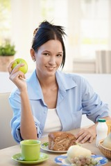 Young woman at breakfast with apple