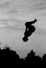Fototapete - silhouette of gymnast on trampoline in sky doing back somersault