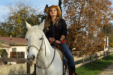 Cowgirl sitting on a white horse