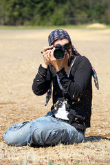 Young woman with DSLR camera outdoors