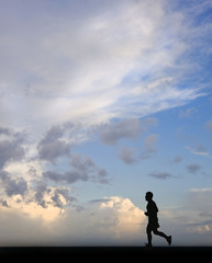 Silhouette of single male jogger against stunning blue sky