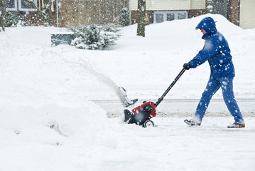 Man Clearing Sidewalk with a Snow Blower
